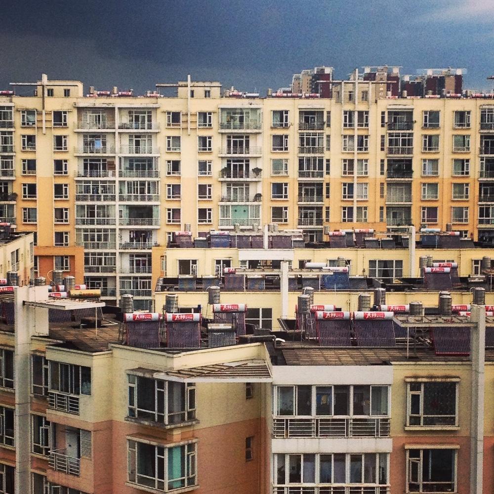 En till balkongutsikt. Observera de röda grejerna på taken, där värms varmvatten av solen. Ekotänk!