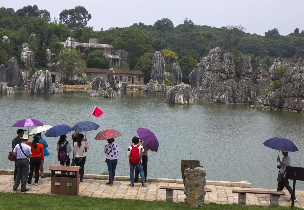 I Kunming där det kan växla snabbt mellan brännande sol och regn har alla alltid ett paraply med sig.