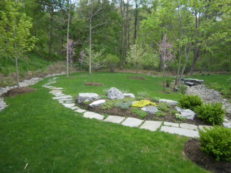 Irregular flagstone pathway, rock garden planted with sedum and catmint, redbud, serviceberry and crabapple trees.