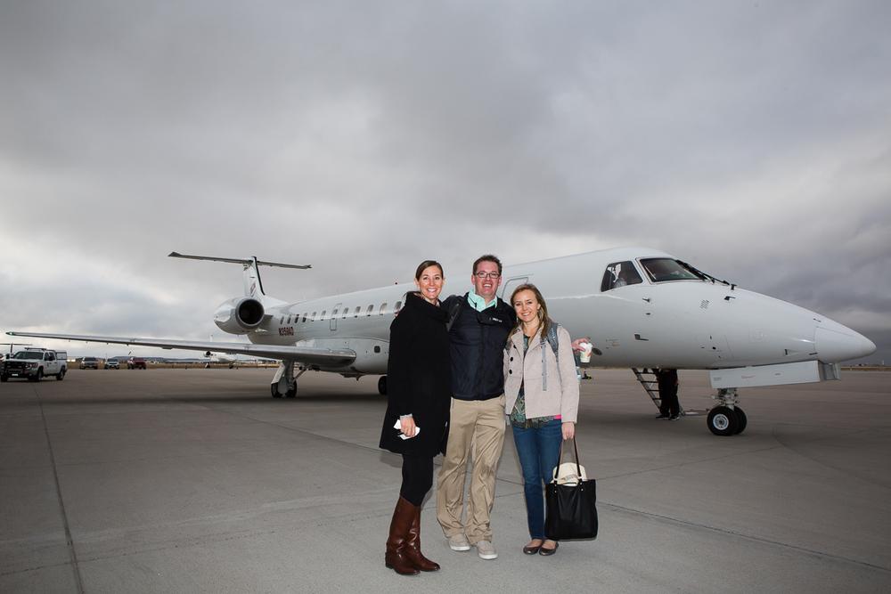 NextGreatTrip staff with Embraer 50-passenger airplane in background