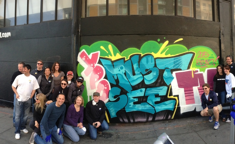 "The group and the graffiti wall they created with the help of local graffiti artist ""Joker"""