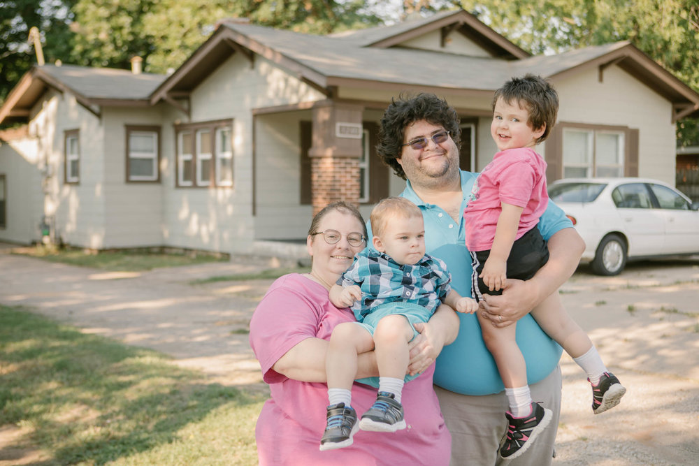 Nathan and Janettee with their two kids in front of their completely renewed home. Serve More Volunteers were able to correct all the code violations that threatened the family's eviction.