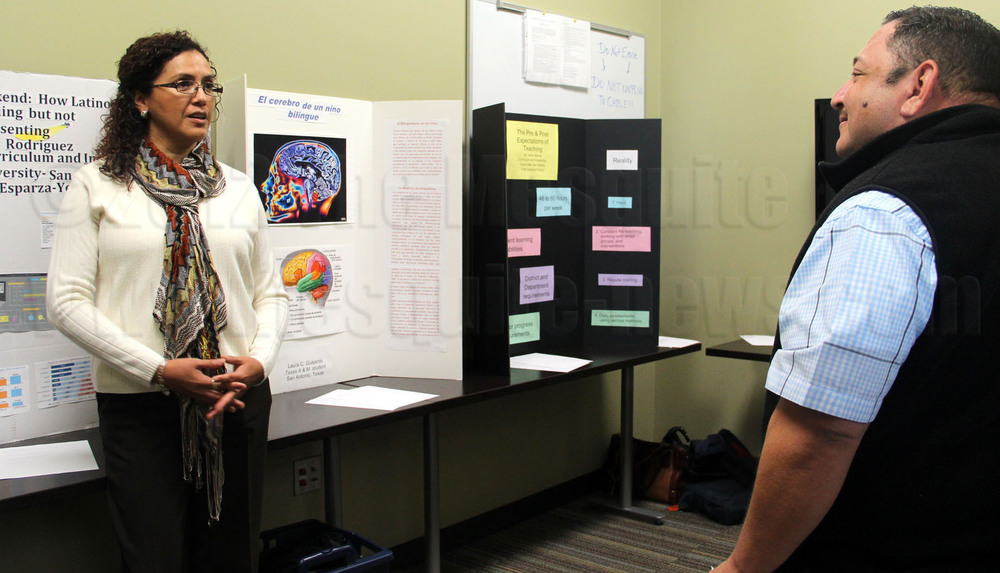 Bilingual education graduate Laura Guajardo discusses her research about the human brain with Eric Lopez, head of the school of education and kinesiology, on Oct. 27 at the second annual Celebrating the Bilingual Child Conference in Room 111 of Main Campus.