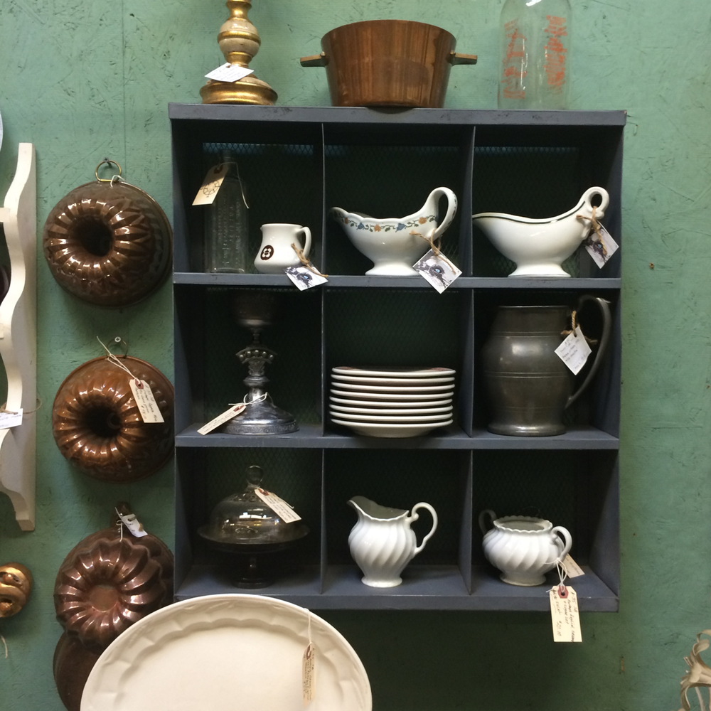 I loved this entire vignette. I've always had a thing for wall hangings with little cubby holes where you can fit all kinds of treasures. I also was intrigued by the aloe wall color and the vintage copper bundt cake pans hung in a trio.