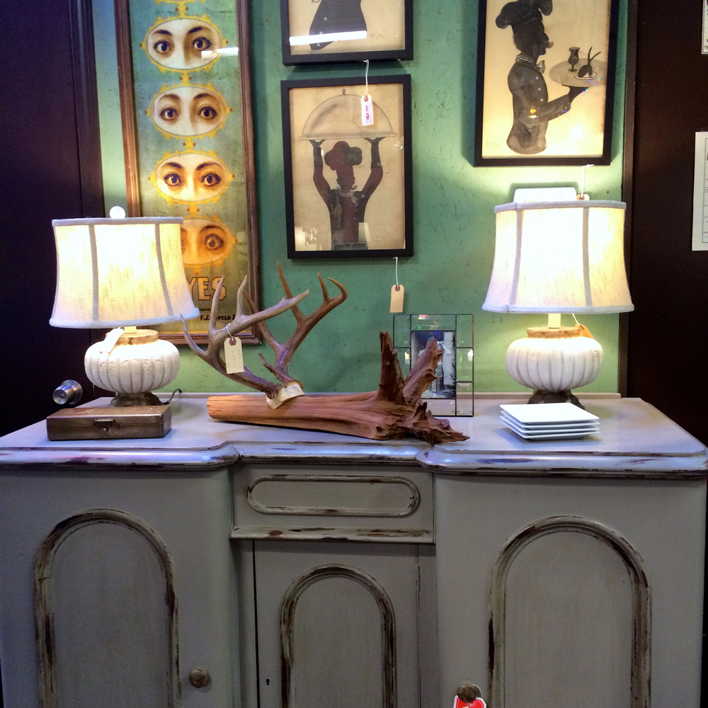 Such a well put together vignette in some of my favorite colors [gray and a light teal/aloe]. The art is quirky, the lamps are traditional, and I'm always down for some horns and driftwood.