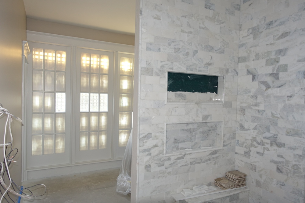 The Windows at the end of the bath are actually doors installed 30 years ago when a former porch was enclosed. The vanity is around the corner from this beautiful shower and we had enough stone from the kitchen counter slabs to use here too.