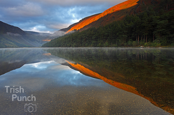 Sunrise water reflections of the upper lake in Glendalough in Wicklow in Ireland.