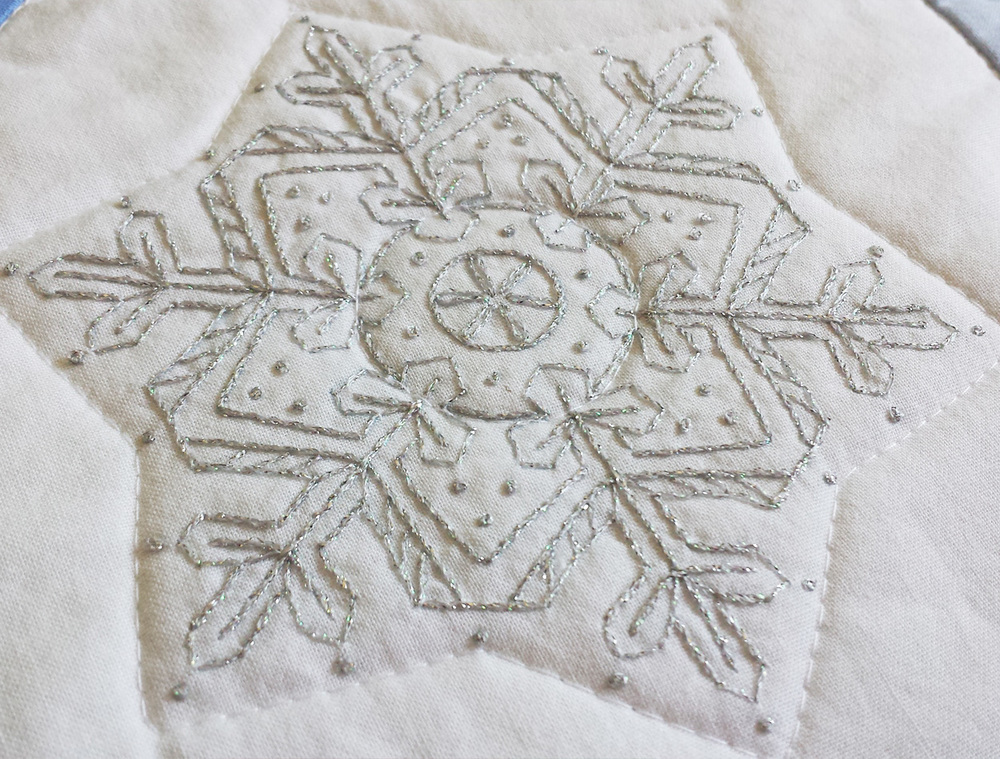 Large snowflake on the quilt using Kreinik floss.