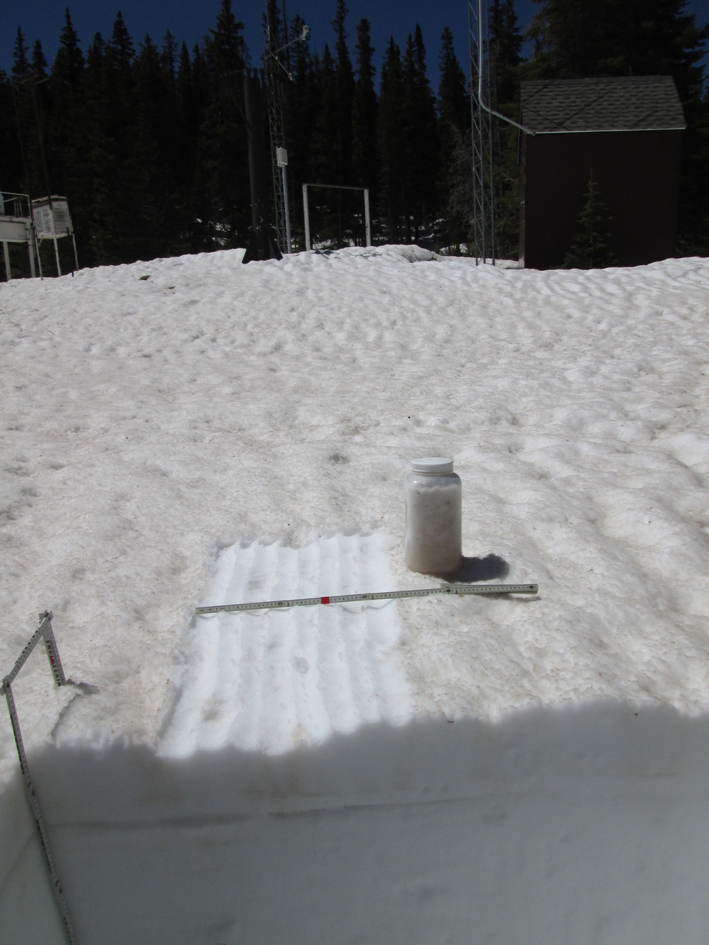 "The 35"" deep snow pit at Berthoud Summit on June 3 contained 15.5"" of SWE, almost exactly matching the SWE being reported at the time by the Snotel just a few yards away.  Merged dust containing at least events D3, D4, and D8 was exposed at the surface and an 'all layers merged' (ALM) sample was collected from an area measuring 1.00 m x 0.48 m, or 0.48 m2.  Dirty melt water from the snow surface had percolated downward in ""preferred flow channels"" into the underlying clean snowcover before spreading laterally at a layer boundary within the snowpack and creating a layer of dust-stained slush, as seen here a few inches below the surface in the snow pit face.   Nonetheless, the ALM sample did capture the vast majority of the merged dust material, for analysis of its chemical and other properties."