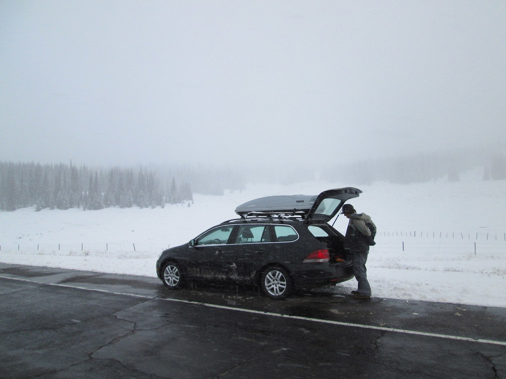 Jay Welz gears up for the Spring Creek Pass snow profile to be performed on the open slope seen in the distance, to the left of the car.