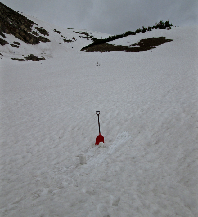 "A site above treeline and adjacent to Pass Lake, just west of the Loveland Pass summit, was utilized to collect an ""all layers merged"" sample of dust layer D3 potentially merged with layers D2 and D1. This site minimized the potential for contamination from the highway corridor.  Recent rains had clearly saturated the snowpack and leached some fine dust material into the snowcover. Dirt and rock entrained in avalanches had also stained the snow seen in the background."