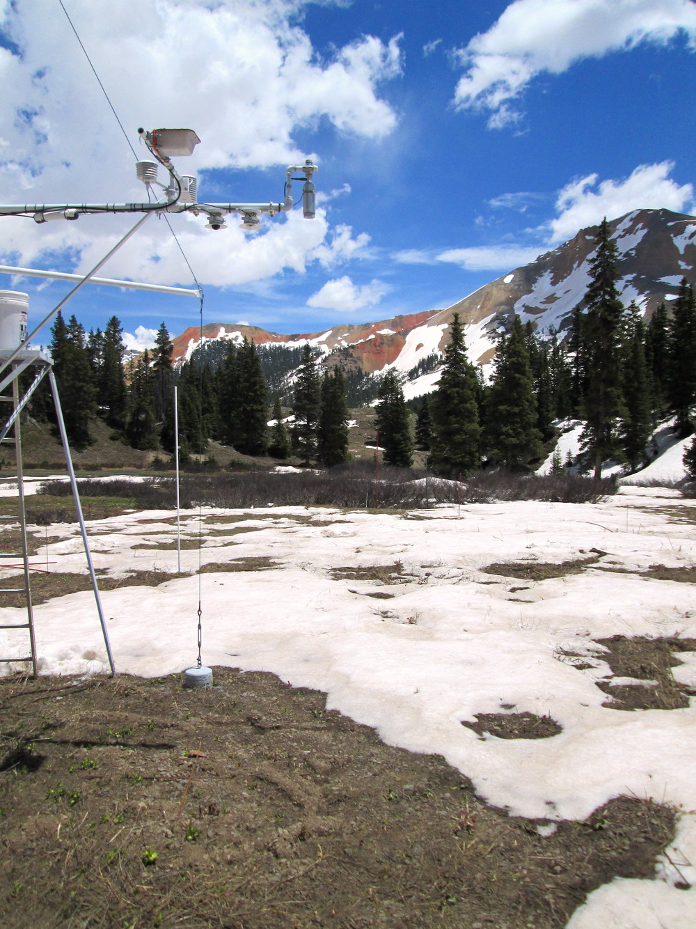 Photo of SASP snow profile sampling area on June 9 with climate station in foreground.  Snow under SR50 snow-depth sensor is now depleted.  Only a few inches of discontinuous snow remains in sample area.