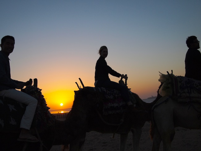 As you do in Morocco: Ride camels on the beach at sundown.