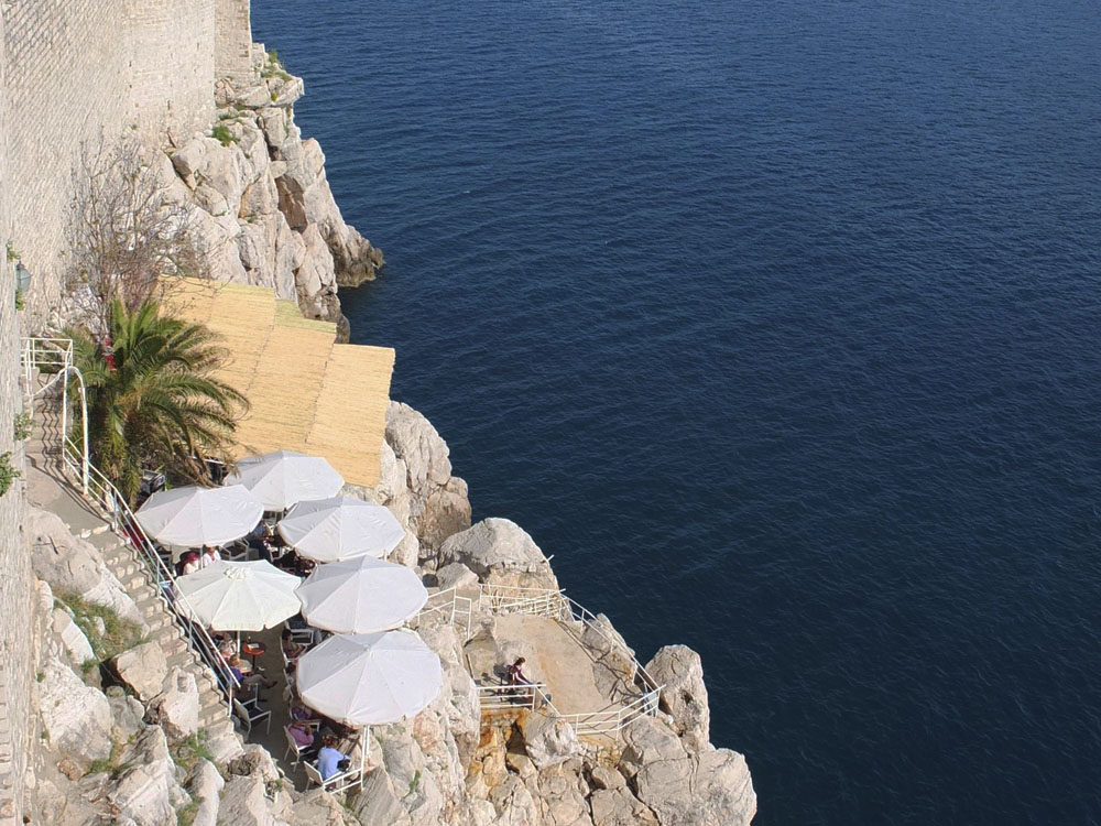 "DRINK // This literal hole-in-the-wall bar — accessed through a hole in the ancient city walls — boasts spectacular views and pricey beer. To find Buza Bar, follow the signs that read ""Cold drinks with the most beautiful view""."