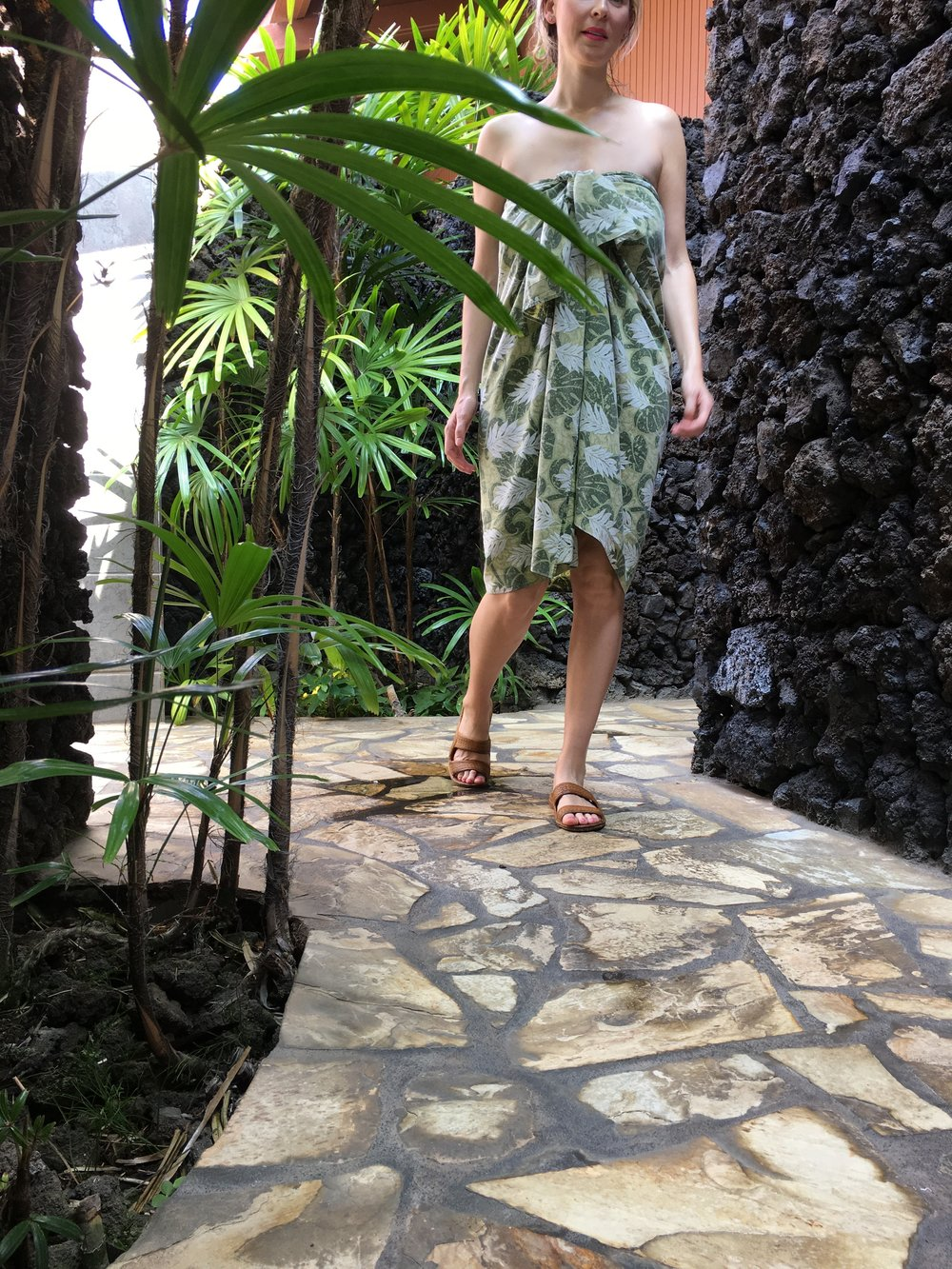 Outfitted in a traditional lava lava, I felt lighter the minute I stepped on the ancient lava flow's grounds graced with thatched-roof huts, pools of orchids, and palms rustling in the wind.
