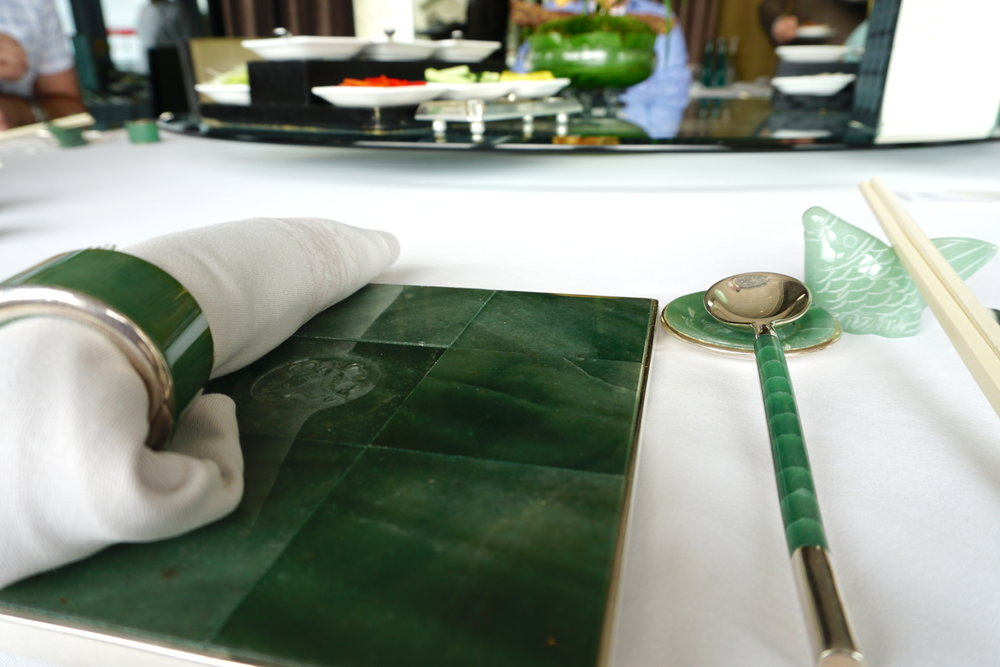 Every place setting is decorated with custom jade tableware, so substantial, it's hard to lift.