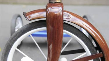 Custom hand painted faux wood grain tricycle image.
