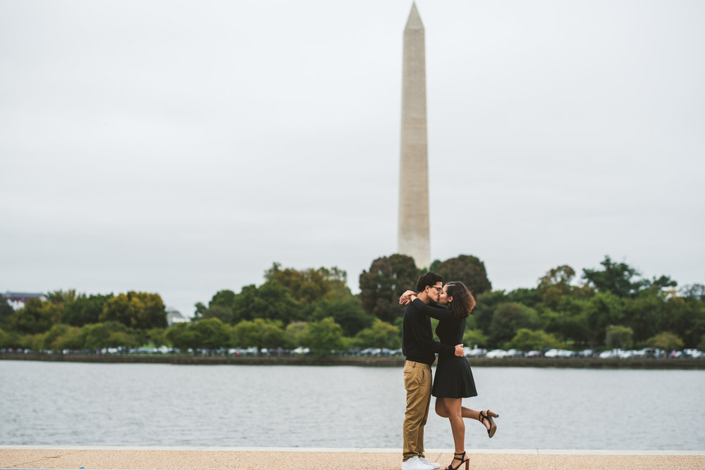 Couple kissing infront of the Washington D.C Monument in the Jefferson Memorial