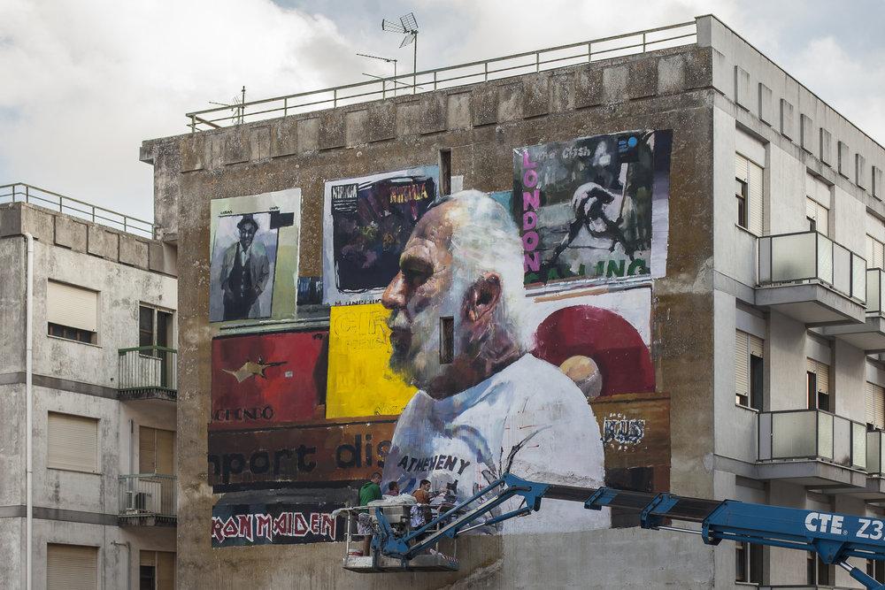 """Il Suonatore Gino"" - WIP mural by Sebas Velasco for the  Festi Wall in Ragusa , Italy.  Photos by  Vinny Cornelli"