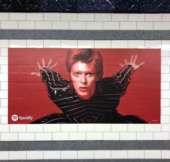 1972: Japanese designer Kansai Yamamoto created a stunning vinyl striped bodysuit for Bowie's Aladdin Sane tour. If you're in NYC, take a ride on the subway to get the full moving image experience. Photo by Masayoshi Sukita.  #DavidBowieIsHere