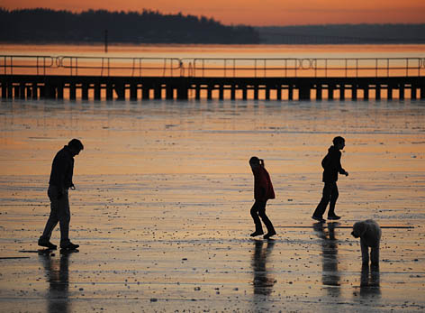 People explore the ice on Lake Washington at Juanita Beach Park in Kirkland on Dec. 11, 2009. (Thom Weinstein, Seattlepi.com)