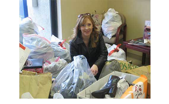 """Jessie Roberson, office manager for the Northwest MLS Grant County satellite office in Moses Lake, sorts donations for the """"Project Haiti"""" shoe drive."""