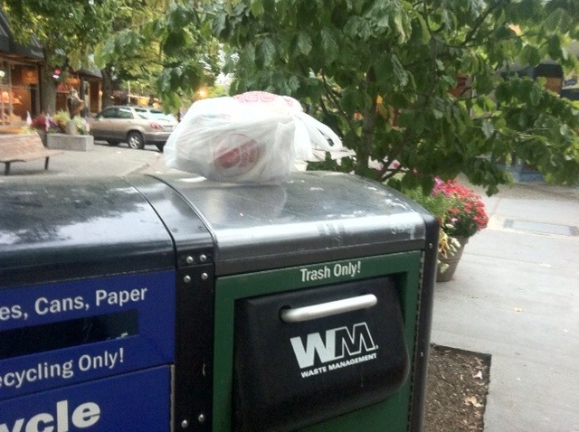 A bag containing a Happy Meal is left on top of a new trash can because it cannot fit inside the new smaller door.
