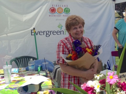 Long-time community volunteer, Virginia Woods, welcomes shoppers to the market.
