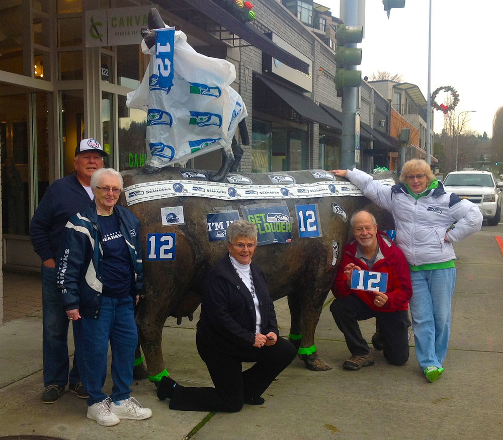 Sants Contreras, Bonnie Fletcher, Sue Contreras, Glenn Peterson and Terri Fletcher spruce up Kirkland's Cow And Coyote statue in preparation for the big game this weekend.