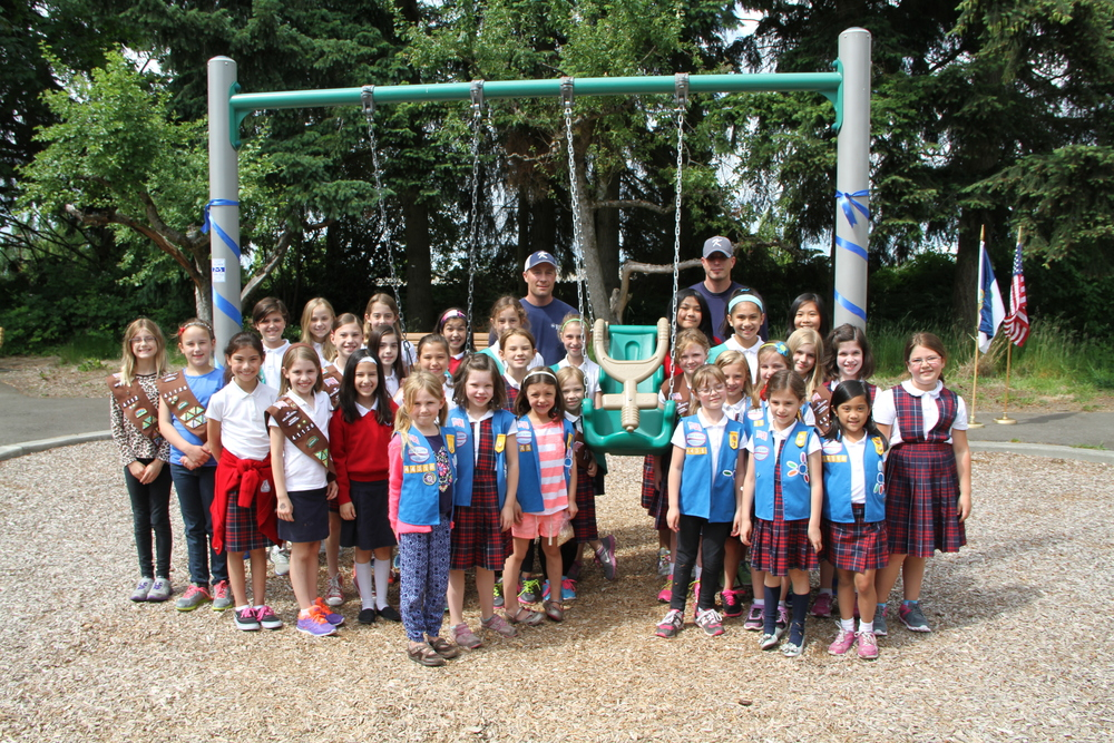 Members of the Holy Family Parish Brownie & Daisy Girl Scout Troops proudly pose with Jim Fitzpatrick and Kyle Johnston, Kirkland Parks Operations Division at the newly installed ADA swing at Rose Hill Meadows Park.  The Girl Scout troops raised money to purchase the swing.