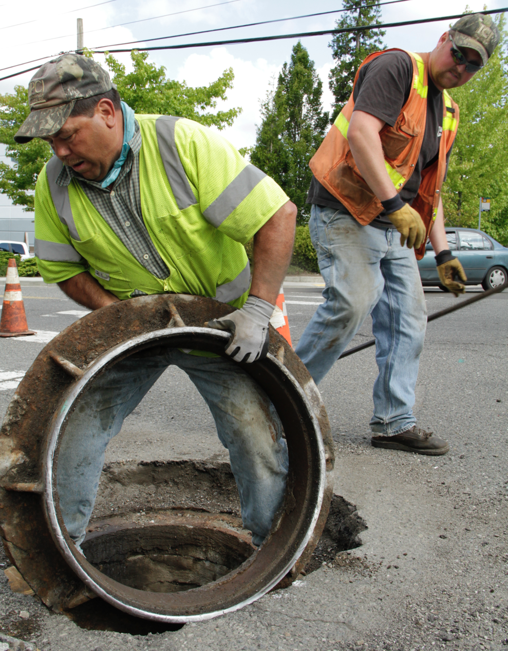 Watson Asphalt operator Chris Schroeder watches as laborer T Pelayo rolls away a sewer drain cover Monday from 120th Avenue Northeast as part of the lowering iron process, in which he and fellow crew members prepare the arterial for grinding later this week. 120th Avenue Northeast is one of six arterials Kirkland is resurfacing this summer. The City of Kirkland is also resurfacing sections of Northeast 112th, 116th and 124th streets, 132nd Avenue Northeast, and Lake Washington Boulevard for a total of 11.8 lane miles.