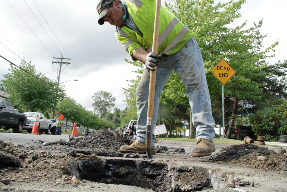 Watson Asphalt laborer T Pelayo digs around a water main utility Monday on 120th Avenue Northeast as part of the lowering iron process, in which he and fellow crew members prepare the arterial for overlay later this week. 120th Avenue Northeast is one of six arterials Kirkland is resurfacing this summer. The City of Kirkland is also resurfacing sections of Northeast 112th, 116th and 124th streets, 132nd Avenue Northeast, and Lake Washington Boulevard for a total of 11.8 lane miles.