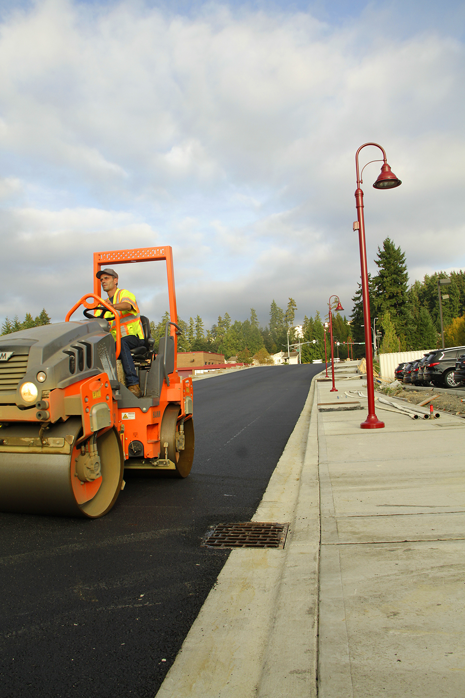 Darin Baker, an operator with Lakeside Industries, compacts on Wednesday afternoon the final layer of asphalt on Northeast 120th Street. The subcontractor paved in two days the 900-foot road extension, which connects 124th Avenue Northeast to Slater Avenue Northeast. The focus of Kirkland's 120th Street contractor now returns to finishing the sidewalk on the north side of the road, as well as installing handrails, traffic signals and signs. The contractor is on schedule to stripe the road's two through-lanes, center turn lane and bike lanes by December.
