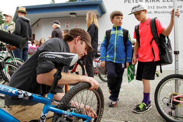 Kirkland Cycle mechanic Matt Caracoglia, left, tunes the bike of Sam Schwarz, pictured in the blue jacket, as Chase Martin, right, looks on. Kirkland Cycle volunteered time and expertise at Peter Kirk Elementary Oct. 9 as part of the annual Walk to School week. Caracoglia and fellow Kirkland Cycle mechanic Garrett Stuart tuned seven bikes in 45 minutes.