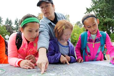 Camille Quelquejeu, from left, Liane Marques, Anna Brundage and Skylr Allen identify their walk routes to school Oct. 9 on a map of the Peter Kirk Elementary School vicinity. Scores of Peter Kirk students have traced their routes on the map using pens and sticky dots as part of the annual Walk to School week.