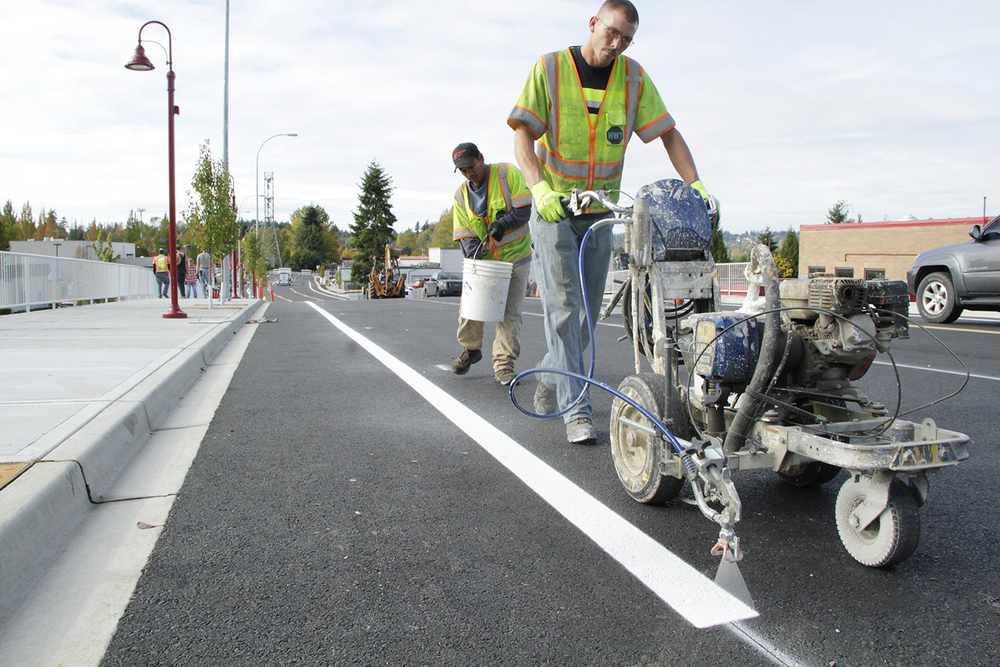 Northwest Traffic's striper Kevin Koepke paints on Oct. 27 the eastbound bike lane on the 800-foot extension to Northeast 120th Street, while laborer Easler Kemai increases the markings' visibility by spreading a powdered glass over it. The City of Kirkland is hosting on Nov. 19 a road-opening event on Northeast 120th Street . Members of the City Council will participate. Kirkland's contractor is nearing completion on the new road, which connect Slater Avenue Northeast to 124th Avenue Northeast in Totem Lake.