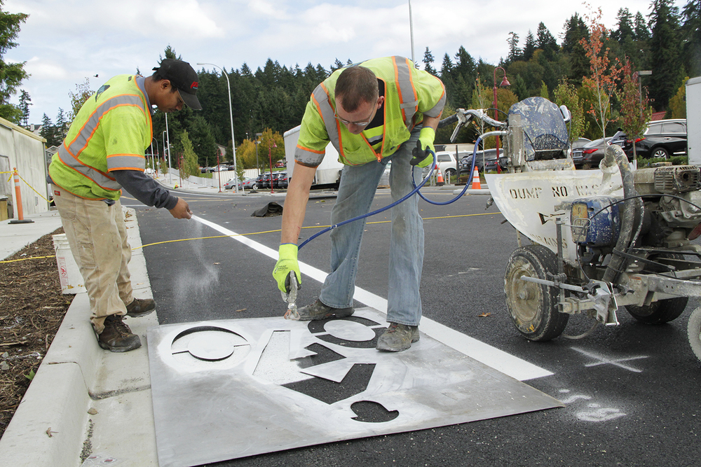To increase its visibility, Northwest Traffic laborer Easler Kemai on Oct. 27 dashes powdered glass onto the bike symbol striper Kevin Koepke paints into the westbound lane of the 800-foot extension to Northeast 120th Street. The City of Kirkland is hosting on Nov. 19 a road-opening event on Northeast 120th Street . Members of the City Council will participate. Kirkland's contractor is nearing completion on the new road, which connect Slater Avenue Northeast to 124th Avenue Northeast in Totem Lake.