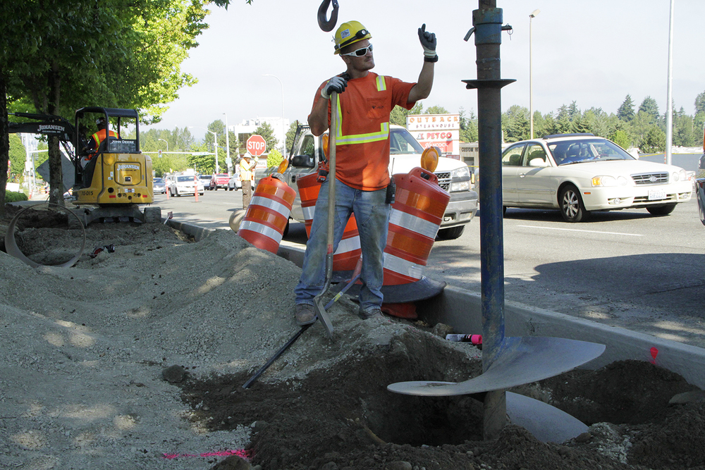 Steve Nicolini, an apprentice electrician directs on Tuesday morning an auger that is drilling a 54-inch-deep hole for the foundation of an 85th Street street light, near 122nd Avenue Northeast. Kirkland's City Council voted unanimously on June 16 to cut 50 days of paving down to 30 nights of paving on Northeast 85th Street. Project engineers expect the paving to start as early as September.