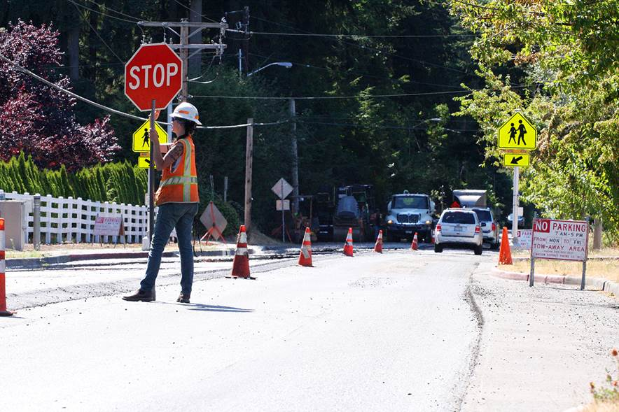 Flagger April Goldsmith, 43, directs traffic through the Northeast 60th Street construction zone. Watson Asphalt will finish repaving the Bridle Trails street this week and begin preparing Kingsgate's Northeast 144th and 143rd Streetfor repavingon Monday.