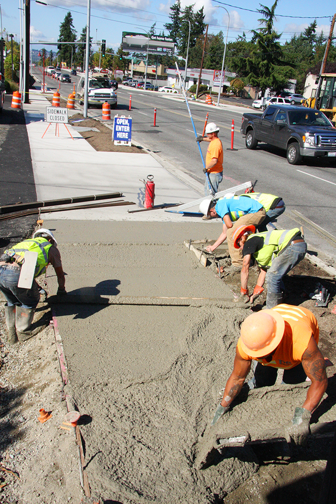A Highlight Concrete crew completes a missing section of sidewalk Sept. 22 on Northeast 85th Street near the Red-Rose Chiropractic Clinic. The crew is finishing all of the sidewalk on 85th Street's south side this week. Meanwhile, 85th Street's repaving process begins this week. Cemex plans to begin grinding 85th Street's top two inches of pavement Thursday night.