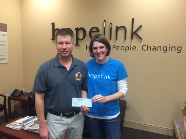 Captain Greg Picinich handing over a check for $1000 to Hopelink.
