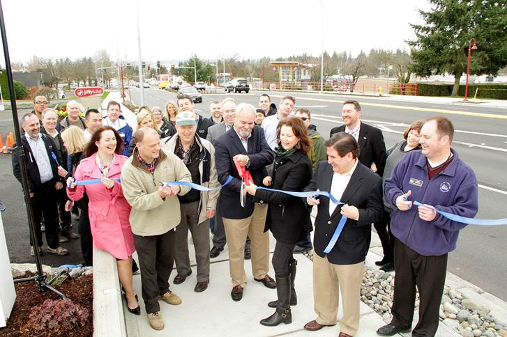 Members of Kirkland's city council, its staff and Honda of Kirkland owner Larry Mallory cut the ceremonial ribbon celebrating the Northeast 85th Street corridor project's completion. Pictured in the front row from left to right are City Council Member Shelley Kloba, Capital Projects Supervisor Rod Steitzer, Capital Projects Manager Dave Snider, Honda of Kirkland owner Larry Mallory, Mayor Amy Walen, Deputy Mayor Jay Arnold and City Manager Kurt Triplett.