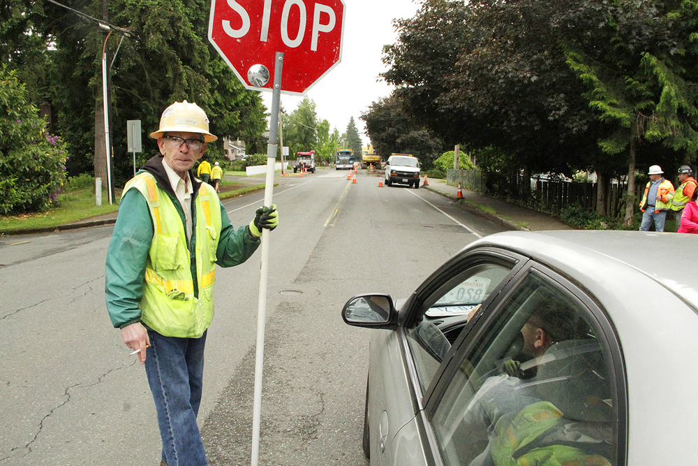 Flagger Ed McNerney stops a driver May 16 on Northeast 80th Street to tell him the wait for an open lane will be 15 minutes. The operation to upgrade the water main has required at least one lane along Northeast 80th Street. Starting May 23, however, it will require two. Shoreline Construction will close Northeast 80th Street for more than two weeks, from the pedestrian bridge to 120th Avenue Northeast.