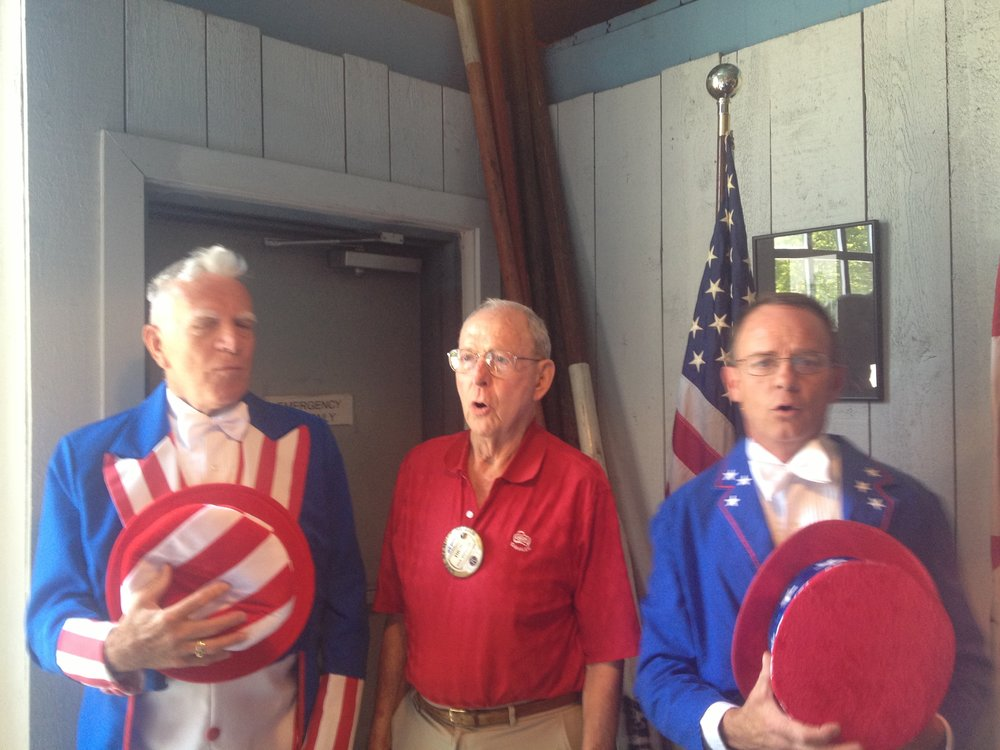 Dick Shinstrom joins his fellow Kiwanis Club members in song celebrating Independence Day.