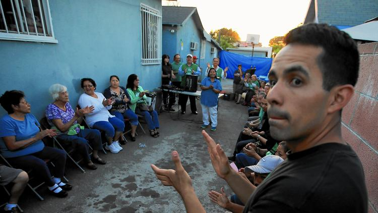 Community members gather at an Eastside home to celebrate the Exide agreement. Residents want the company to follow through on the cleanup of lead in their neighborhoods and homes.    (Luis Sinco / Los Angeles Times)
