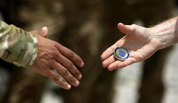 Traditionally the presentation of a challenge coin is passed during a handshake.