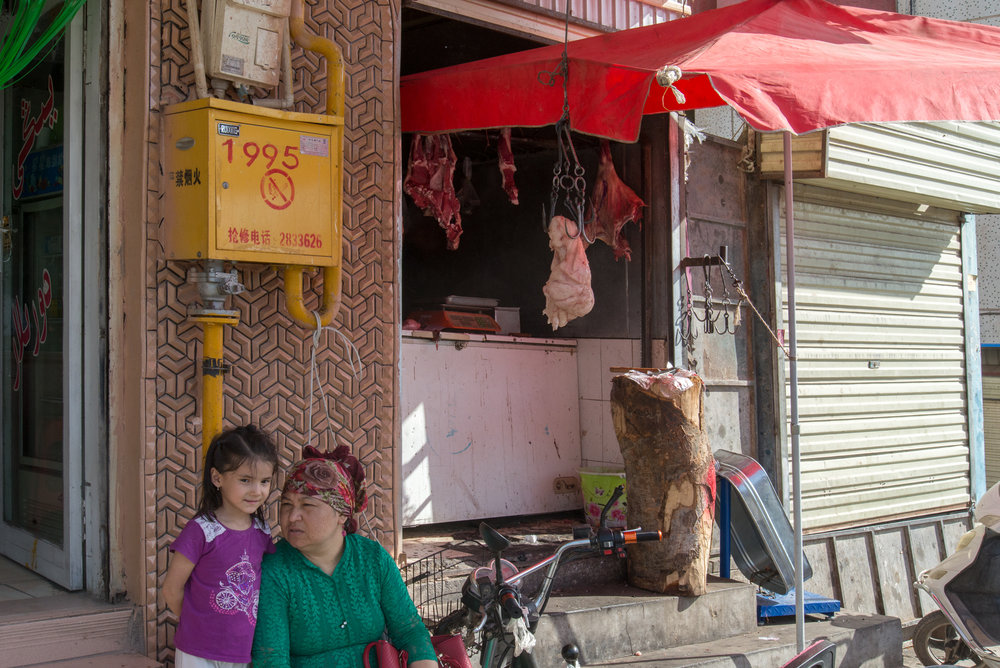 Grandma and Granddaughter in front of butcher shop, Kashgar Baazar