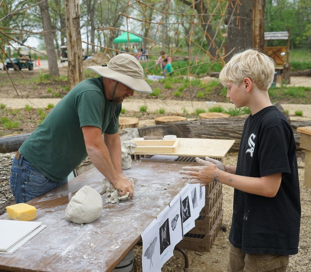 Artist Drew Helge demonstrates working with clay at the grove.
