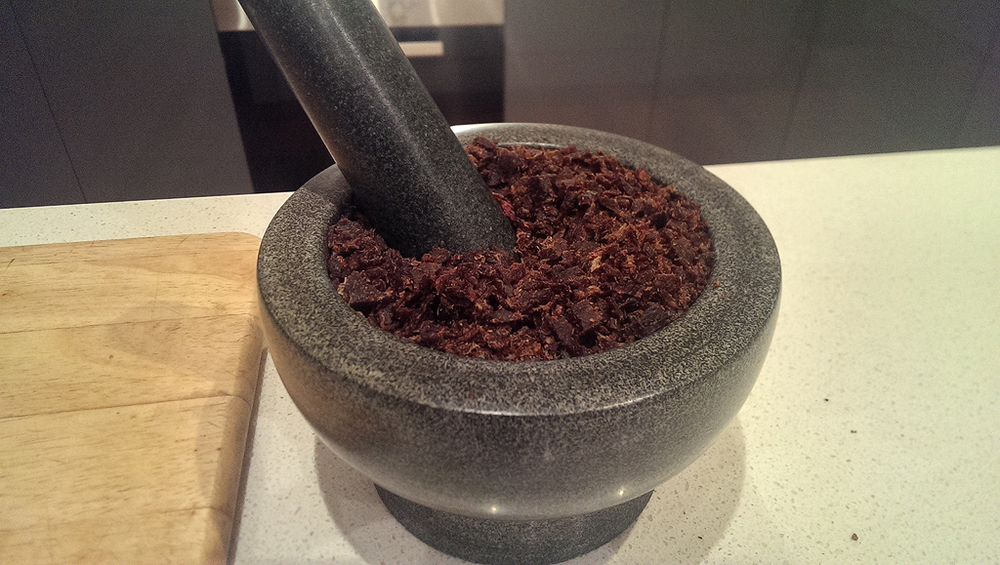 Crushing the beef jerky in a pestle