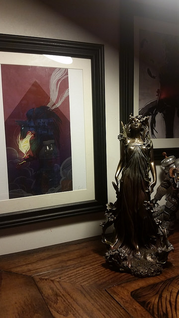 Anubis by Kim Herbst, and a brass statue of Alphonse Mucha's artwork